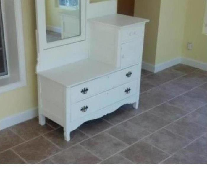 a white antique vanity restored after sustaining fire damage