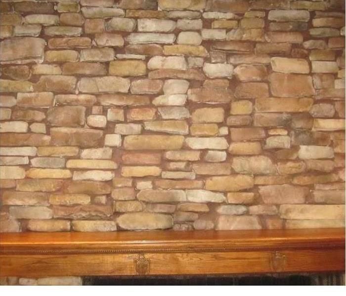 the stone area on a stone fireplace that was once stained by soot has been made clean