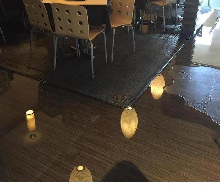a floor with wood floors, a table and lots of water pooling
